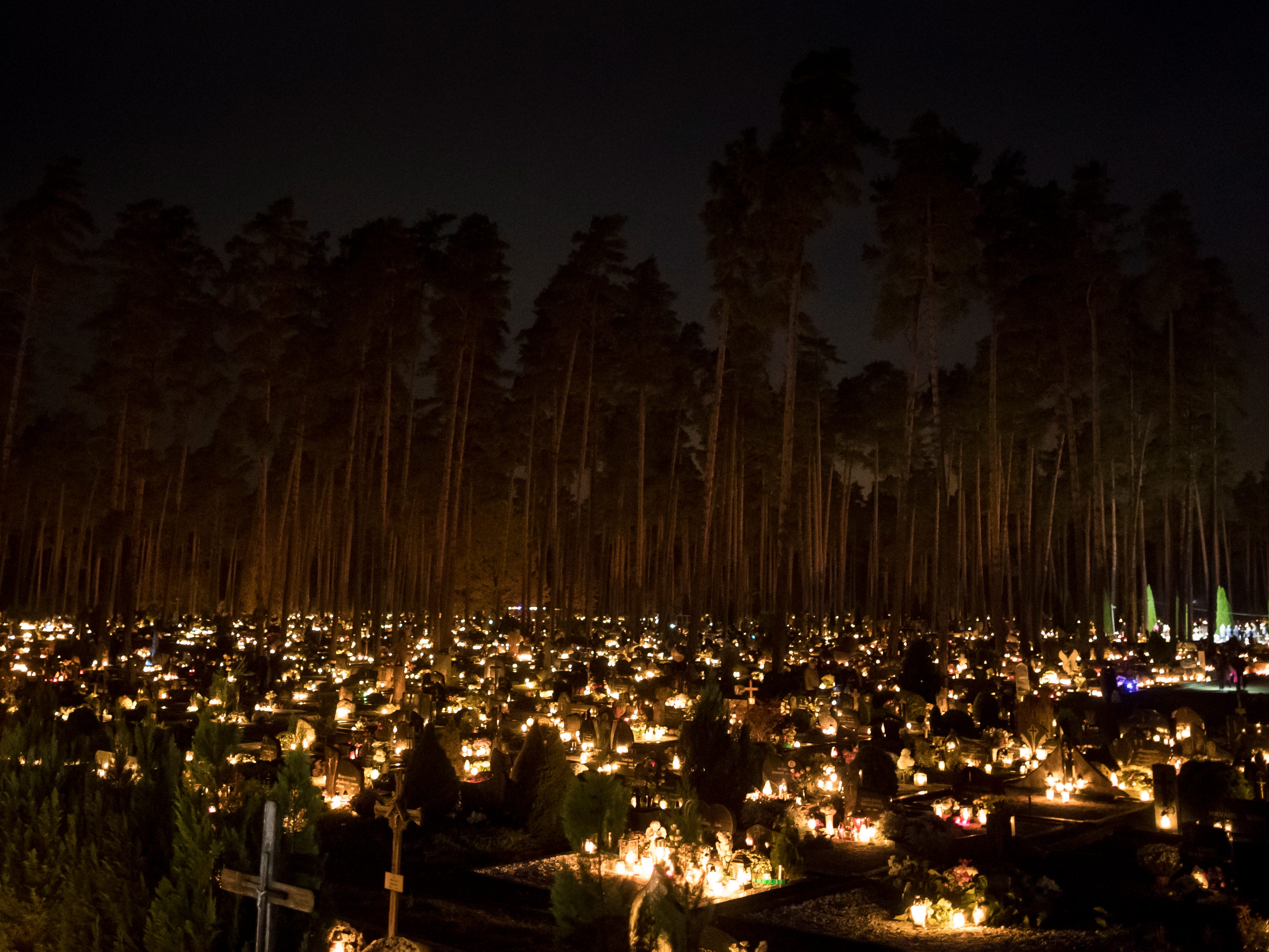 Relatives gather around graves illuminated by candles during All Saints Day at the cemetery in Vilnius, Lithuania, Thursday, Nov. 1, 2018. Candles illuminate tombstones across Europe as people commune with the souls of the dead on Thursday, November 1, 2018, observing one of the most sacred days in the Catholic calendar.