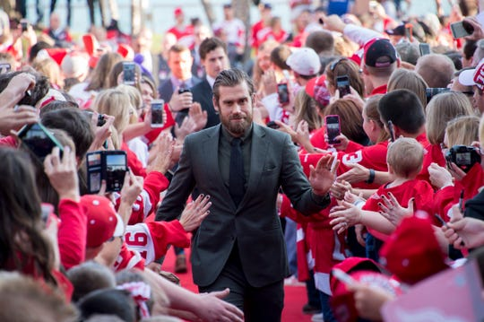 Detroit captain Henrik Zetterberg high-fives fans at Joe Louis Arena during a red carpet arrival for the team before the home opener vs. the Ottawa Senators in 2016.