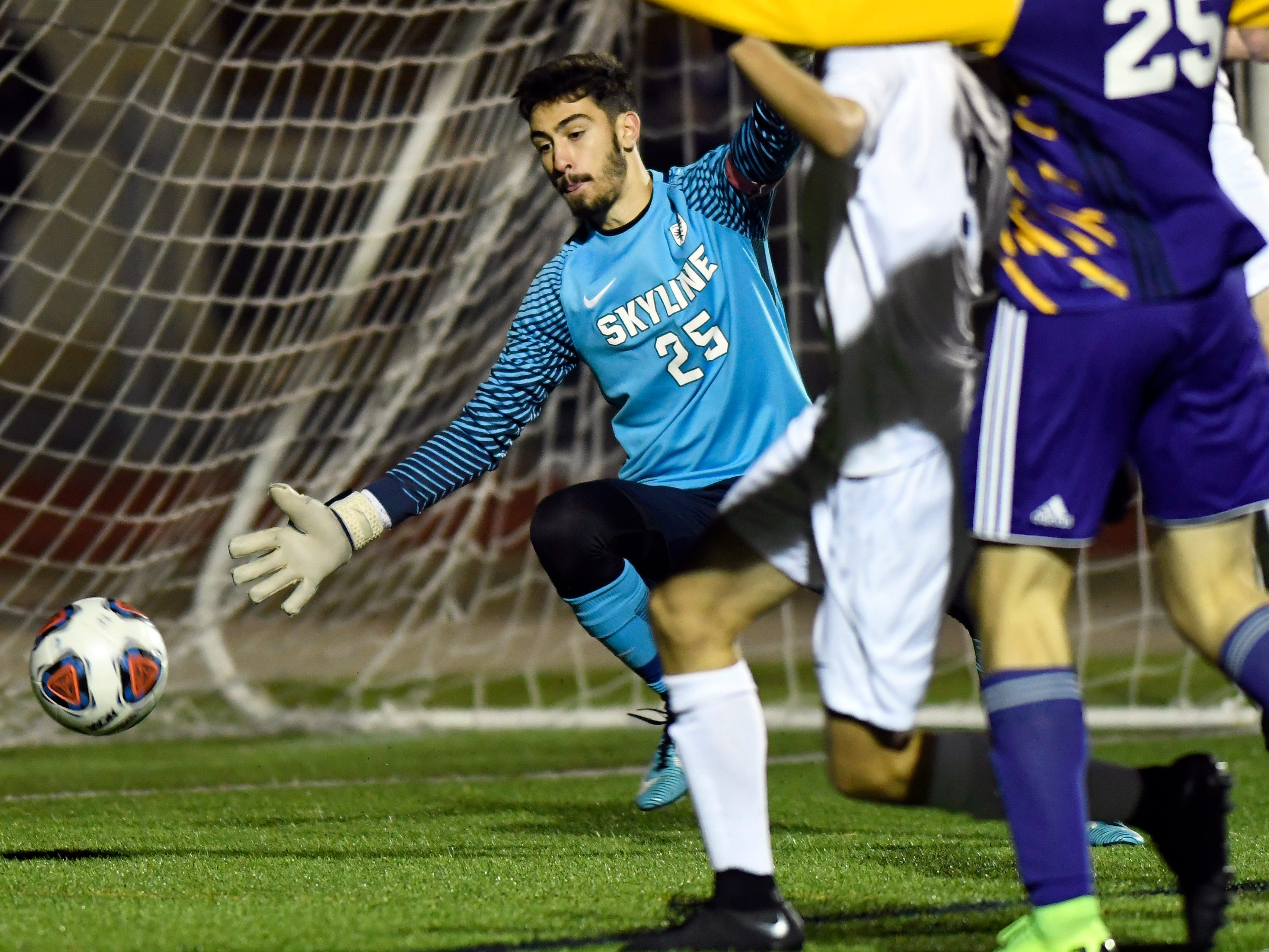 Ann Arbor Skyline goalkeeper Kyri Wixom (25), left, dives to save a shot that goes wide from a Warren De La Salle player in the first half.