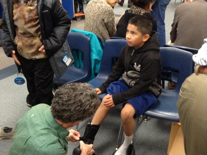 Marcos Duran, a student at Putnam Elementary School, gets fitted for new snow boots Oct. 26. Coats and Boots, a local nonprofit, gave out about 1,000 new coats and pairs of boots this year.