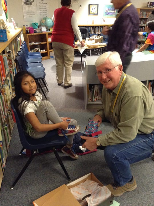 Aleyda Rodriquez, a student at Putnam Elementary School, gets fitted for new boots Oct. 26. Coats and Boots, a local nonprofit, gave out about 1,000 new coats and pairs of boots this year to kids in need.