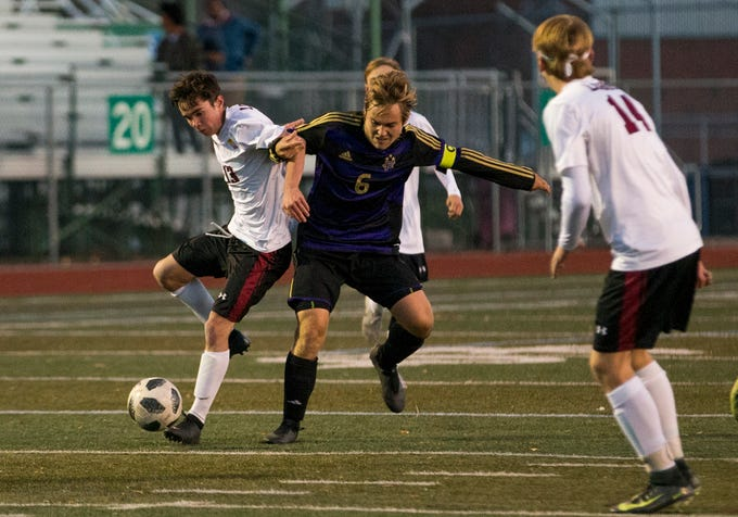 Rocky Mountain's Timmy Thompson (13) and Fort Collins' Alec Fronapfel (6) battle for ball control during the second round of the State Playoffs Wednesday evening Oct., 31, 2018 at French Field in Fort Collins. The Lambkins beat the Lobos 2-0.