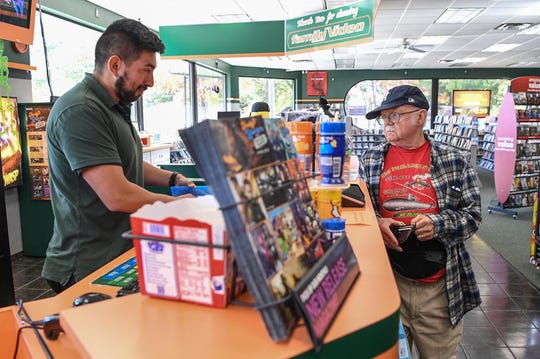 Howard Quintanilla, left, checks out videos for Ron Raymond, right. Quintanilla said nostalgia, and being able to browse the shelves, are big factors in why people come into the store.