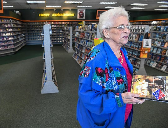 Donna DuPage of Mauldin brings a used movie to purchase up to the counter at the Family Video store in Mauldin.