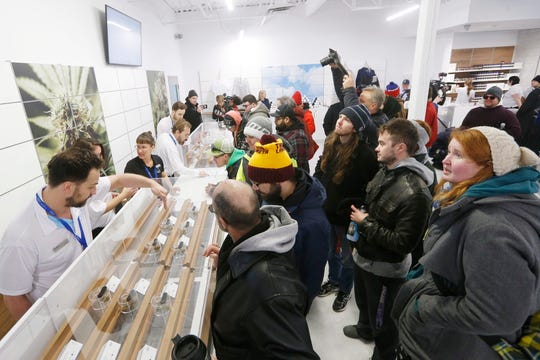 In this Oct. 17, 2018, file photo, people check out the sample counter at a cannabis store in Winnipeg, Manitoba. Supply shortages have been rampant in the two weeks since Canada became the largest national pot marketplace.