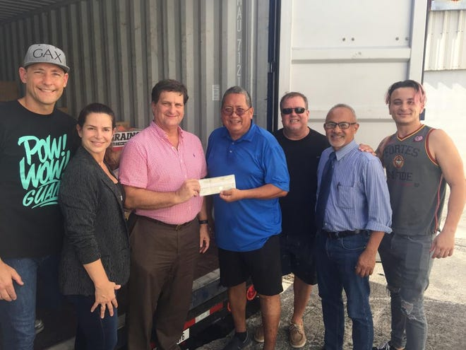 Ayuda Foundation board members accept check from members of the Ysrael family