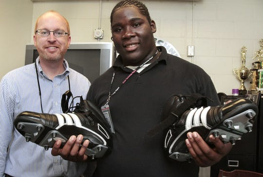 IndyStar columnist Matt Tully, left, poses with Fred Hopkins, 15, who received a new pair of size 21 Adidas athletic shoes on Aug. 31, 2010. Donations poured in for the Arsenal Tech football player with huge feet after a Tully column ran in the Sunday Star days earlier. The shoes are size 20, stretched to size 21 for a better fit to Hopkins' feet. A sophomore, he's the biggest player on the team, at 6 feet, 5 inches and 335 pounds. Hopkins left Manual High School for Tech a few months ago after IPS eliminated Manual's football program.