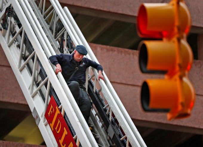 An IFD firefighter descends a ladder as IFD fights a car fire in a parking garage at Illinois and New York, Thursday, Nov. 1, 2018.