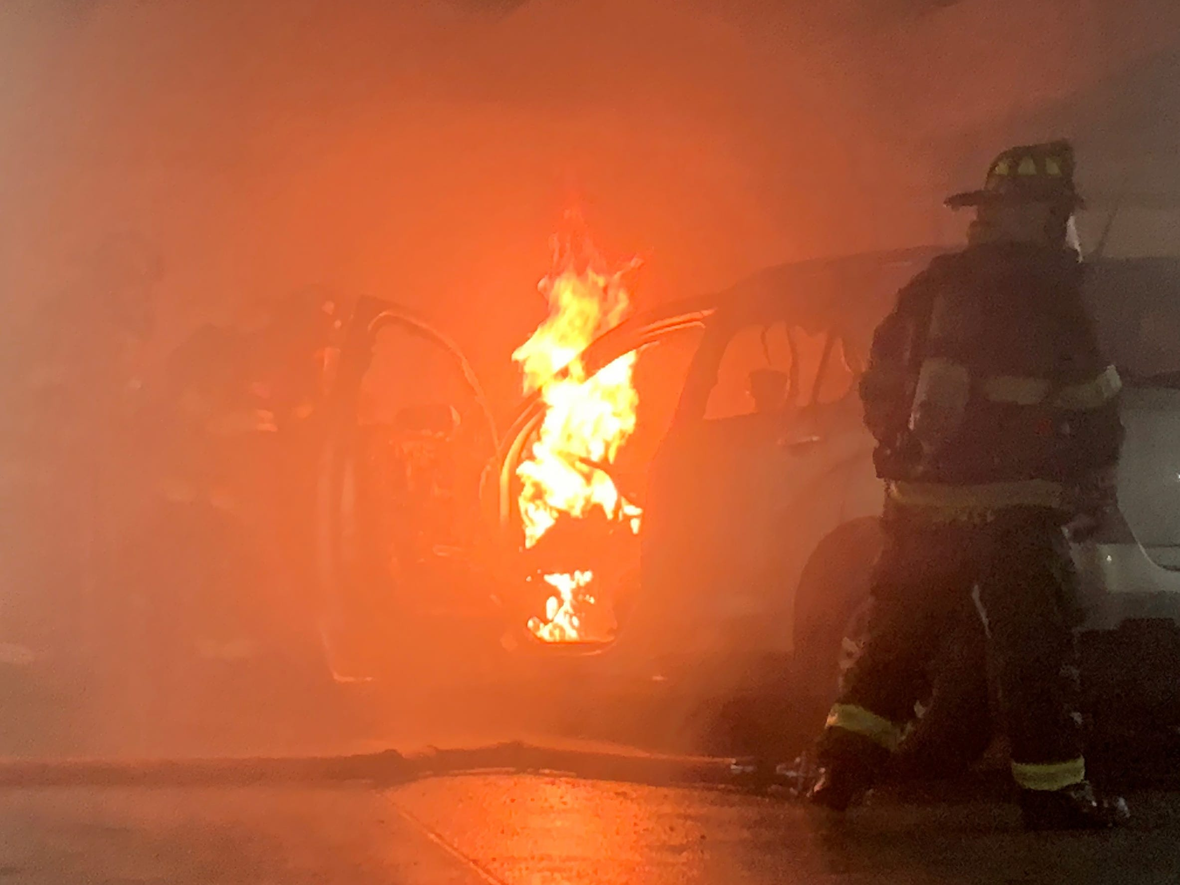 Flames jump from a car as IFD fights a car fire in a parking garage at Illinois and New York, Thursday, Nov. 1, 2018.