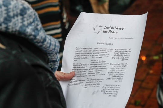 A woman reads the Mourner's Kaddish during a solidarity vigil and public mourning held at the City Market in Indianapolis on Thursday, Nov. 1, 2018.