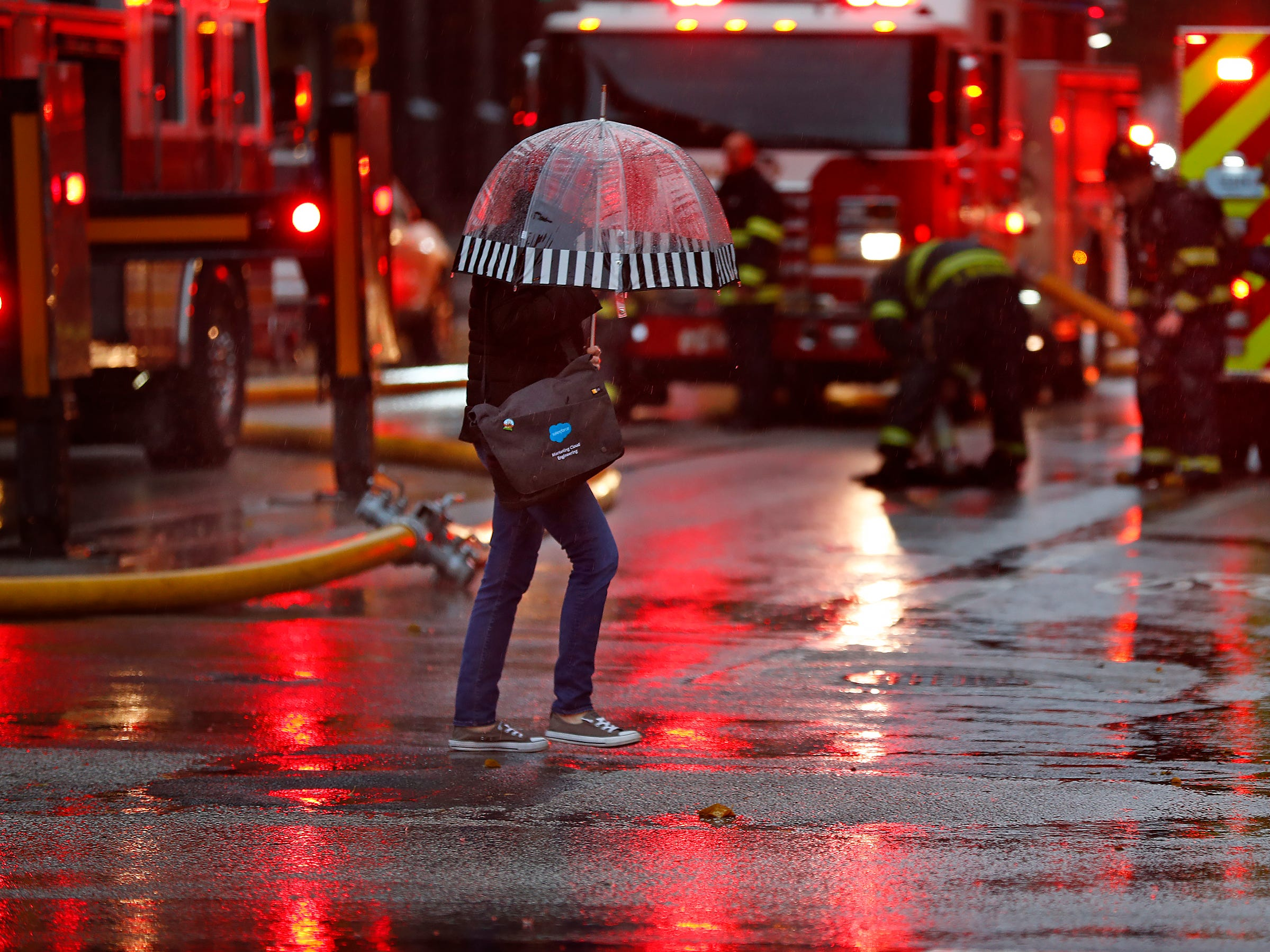 A pedestrian crosses New York on a rain-soaked street red with emergency vehicle lights, as IFD fights a car fire in a parking garage at Illinois and New York, Thursday, Nov. 1, 2018.
