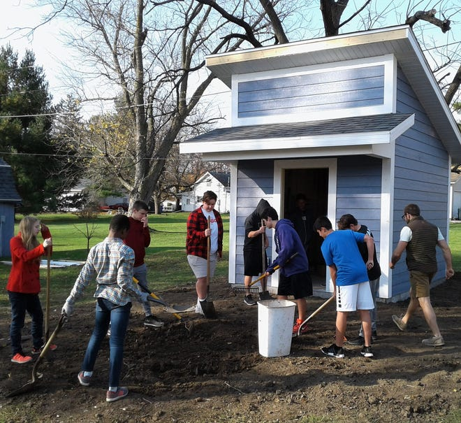 Liberty High School students spent a class period this week cleaning up the construction site around the attractive new garden shed they built at the home of their instructor, Micah Casper