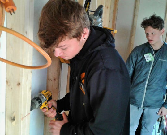 David Allen drills a hole in a stud for an electrical wire in the totally student-built shed at a residential home in North Liberty.  Watching behind him is Izaak Hajek.