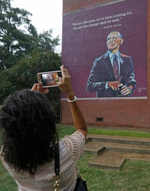 Precious Malembeka, an administrative intern with the Jackson Public Schools, take a smartphone photo of the completed mural of former President Barack Obama, painted on the south side of the Obama Magnet School in Jackson, Miss., Friday, Aug. 17, 2018. The school, was the Jefferson Davis Elementary School until the fall of 2017, when it was renamed after the former president. The husband and wife team of Charles and Talamieka Brice, painted the mural.  (AP Photo/Rogelio V. Solis)