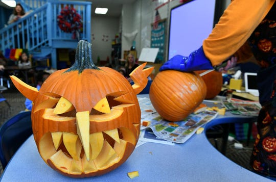 Carved pumpkins are also accepted as donations at Hooves & Feathers. Here, Doctor Carvinstein, Ken Clayton, carves pumpkins for kindergarteners in Stephanie Arms' class Wednesday, October 31, 2018 at A.L. Lotts Elementary School.