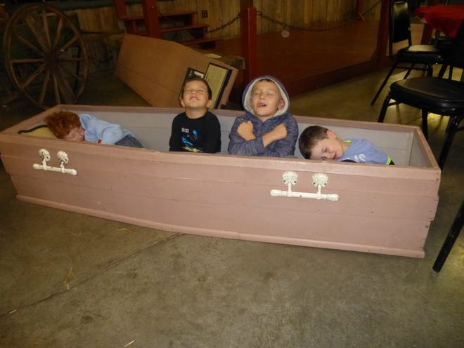 "Cooper Smith, Austen Smith, Lane Thomas and Jase Smith, from left, make their ""test run"" of a 50-year-old homemade coffin during the ""Haunts & History"" festival at the Museum of Appalachia."
