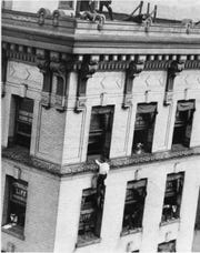 "George Gibson Polley climbs the Burwell Building at the corner of Gay Street and Clinch Avenue, likely during an April 1918 Great Liberty Parade that celebrated America's one-year anniversary of entering World War I. Polley, also known as ""The Original Human Fly,"" was from Marblehead, Mass."