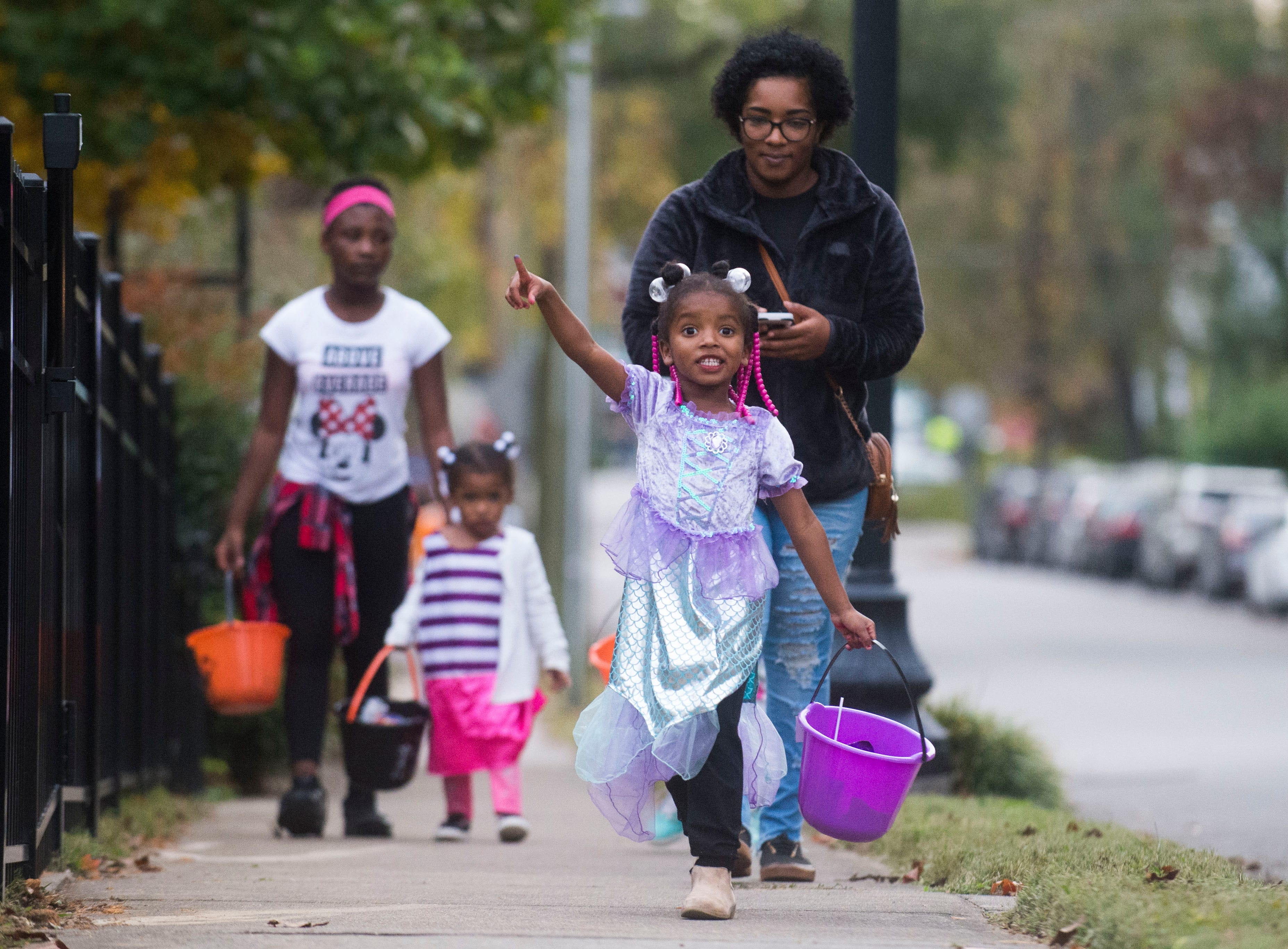 An excited child walks up the sidewalk while trick-or-treating in the Fourth and Gill neighborhood in Knoxville, Wed. Oct. 31, 2018.