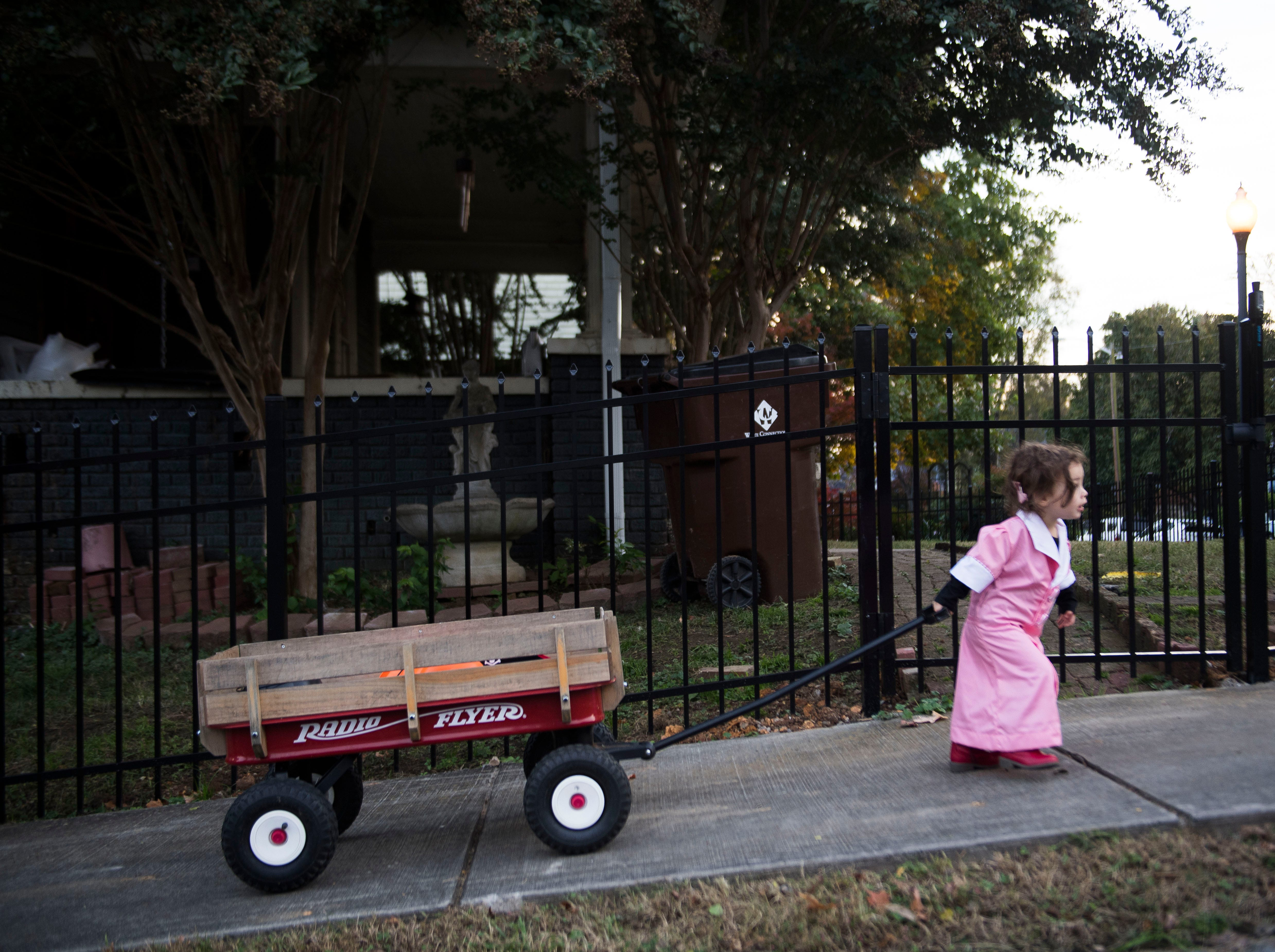 Fiona Granatino, 2, pulls her own wagon up a hill while dressed as a waitress, while trick-or-treating in the Fourth and Gill neighborhood in Knoxville, Wed. Oct. 31, 2018.