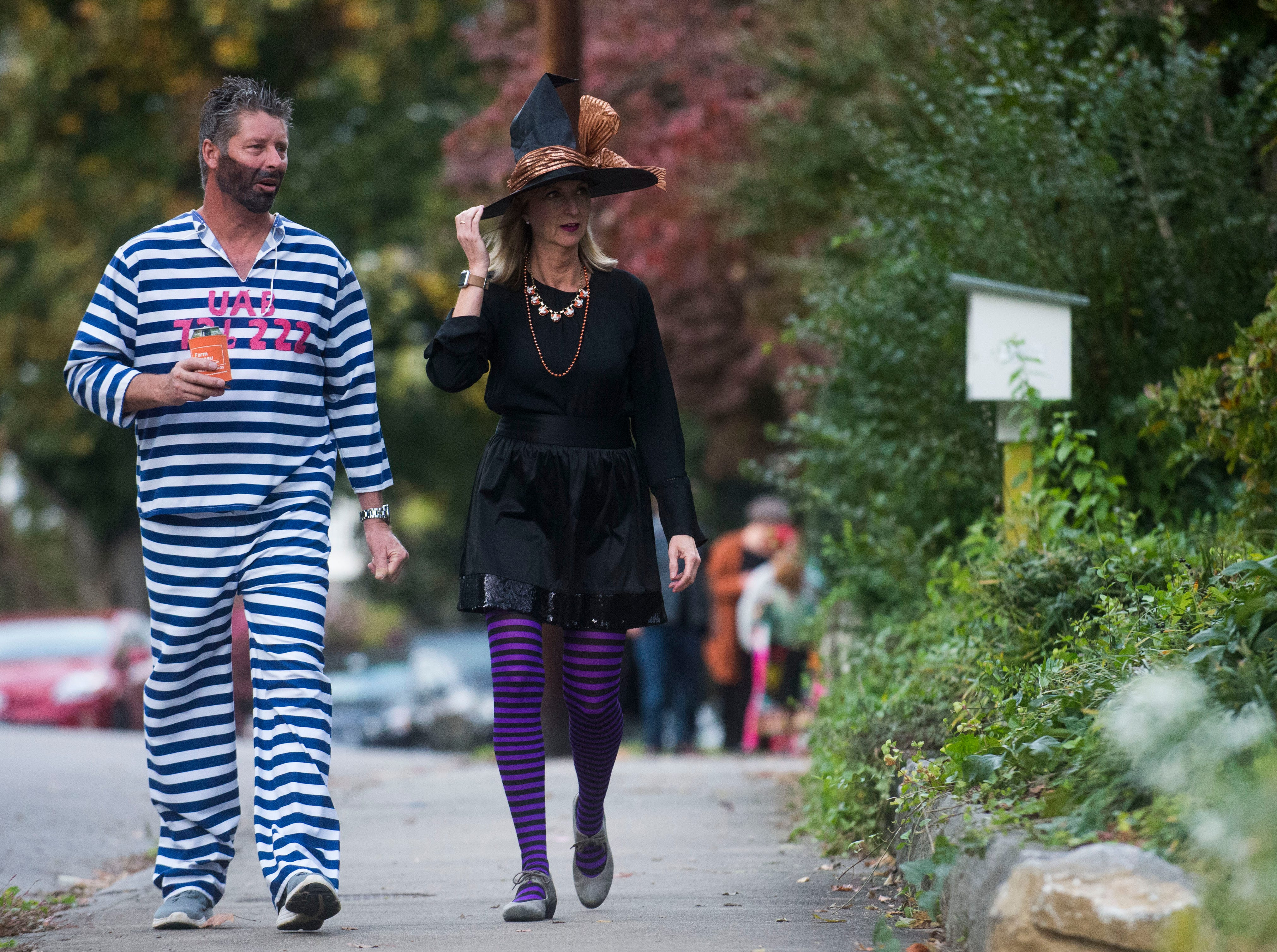Remy and Susan Hebert walk towards a party in the Fourth and Gill neighborhood in Knoxville, Wed. Oct. 31, 2018.