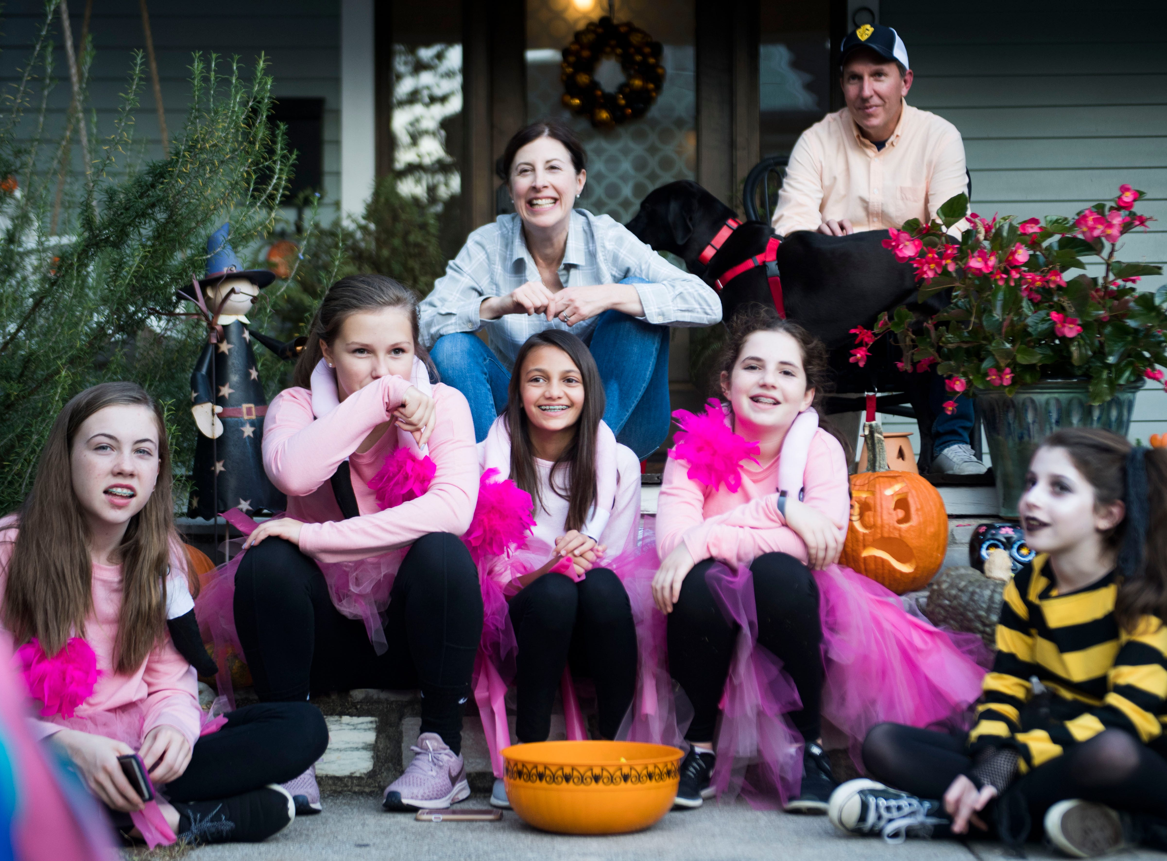 A flock of pink yard flamingos and a zom-bee wait for children to trick-or-treat in the Fourth and Gill neighborhood in Knoxville, Wed. Oct. 31, 2018.