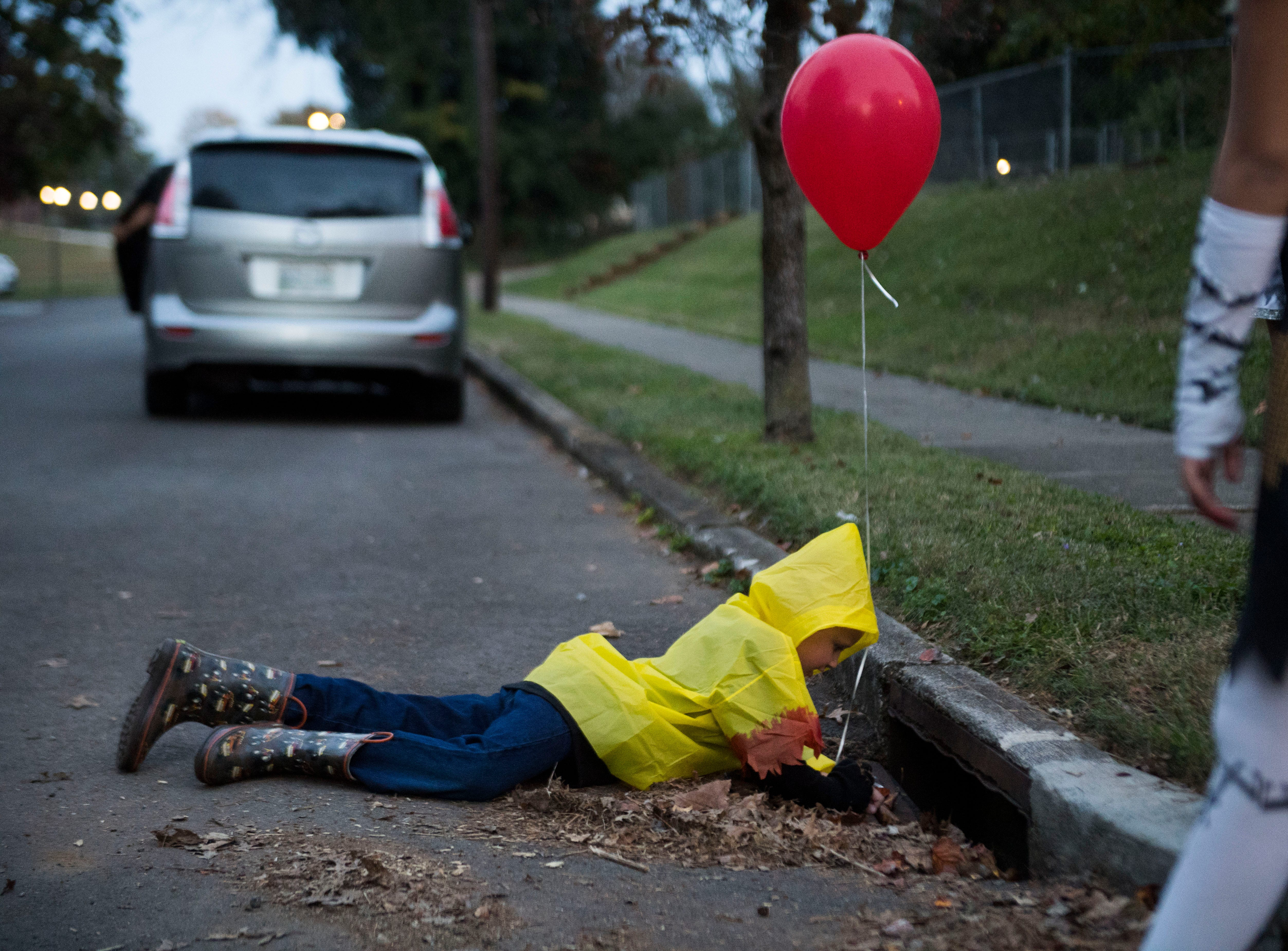 """Christopher Breeden, 7, dressed as Georgie from the movie """"It"""" poses for a photo while trick-or-treat in the Island Home neighborhood in Knoxville, Wed. Oct. 31, 2018."""