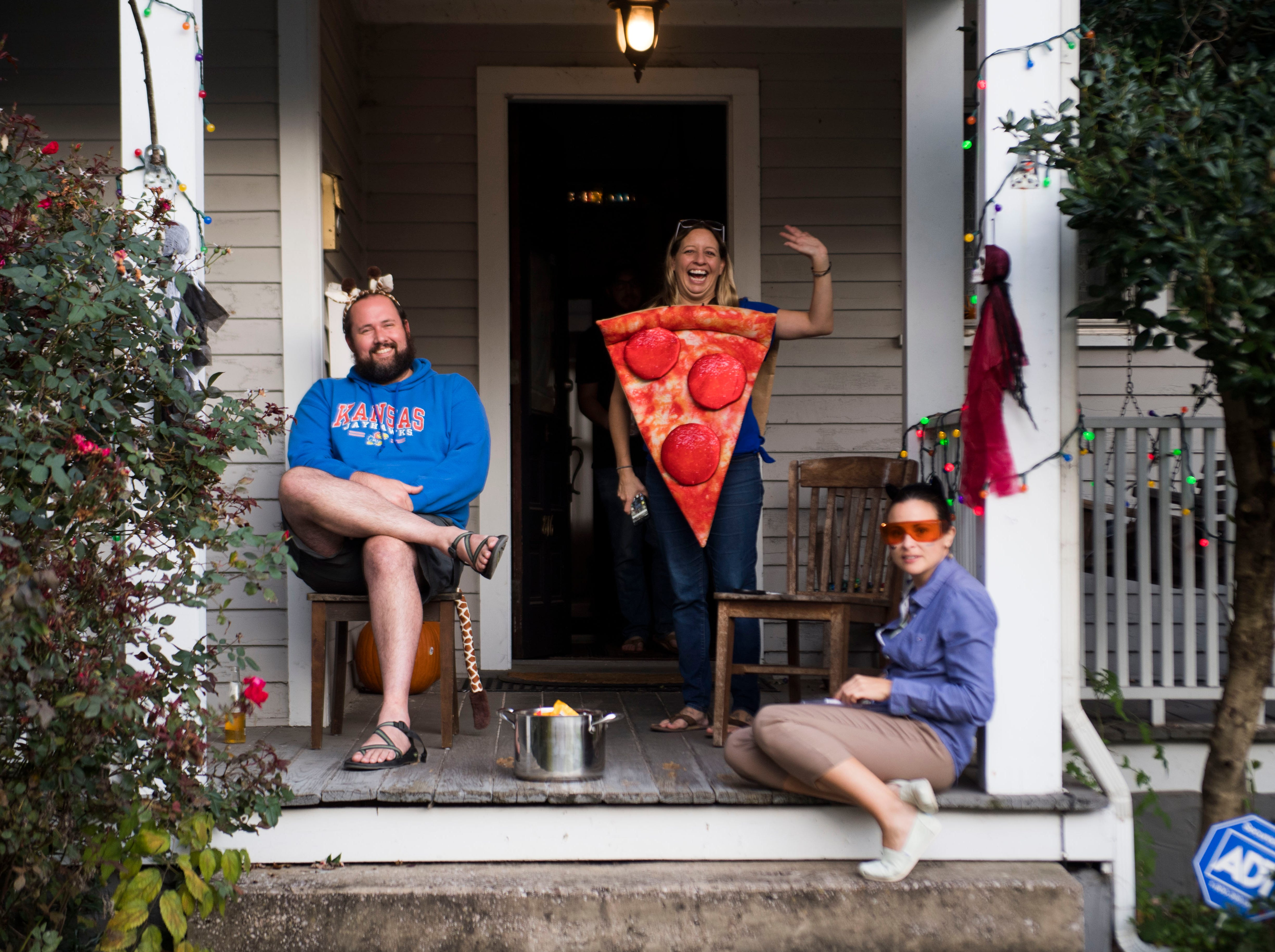 From left Tyson Paulson, Katie Kulhaui, Jess Welch, wait for children to trick-or-treat in the Fourth and Gill neighborhood in Knoxville, Wed. Oct. 31, 2018.