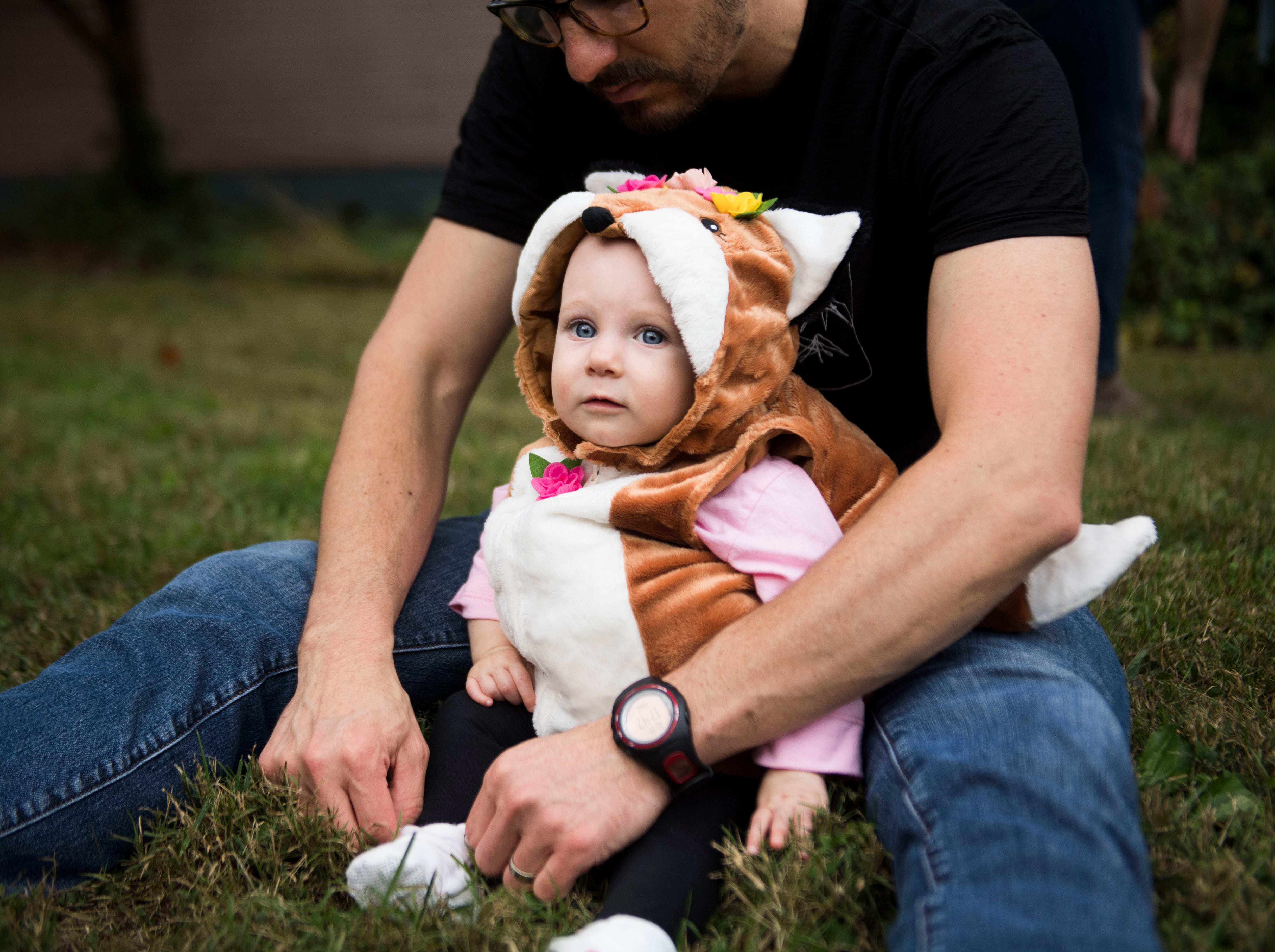 Joel Stefanini adjusts the costume of his daughter Lia, 1, at the Fourth and Gill neighborhood Halloween party in Knoxville, Wed. Oct. 31, 2018.