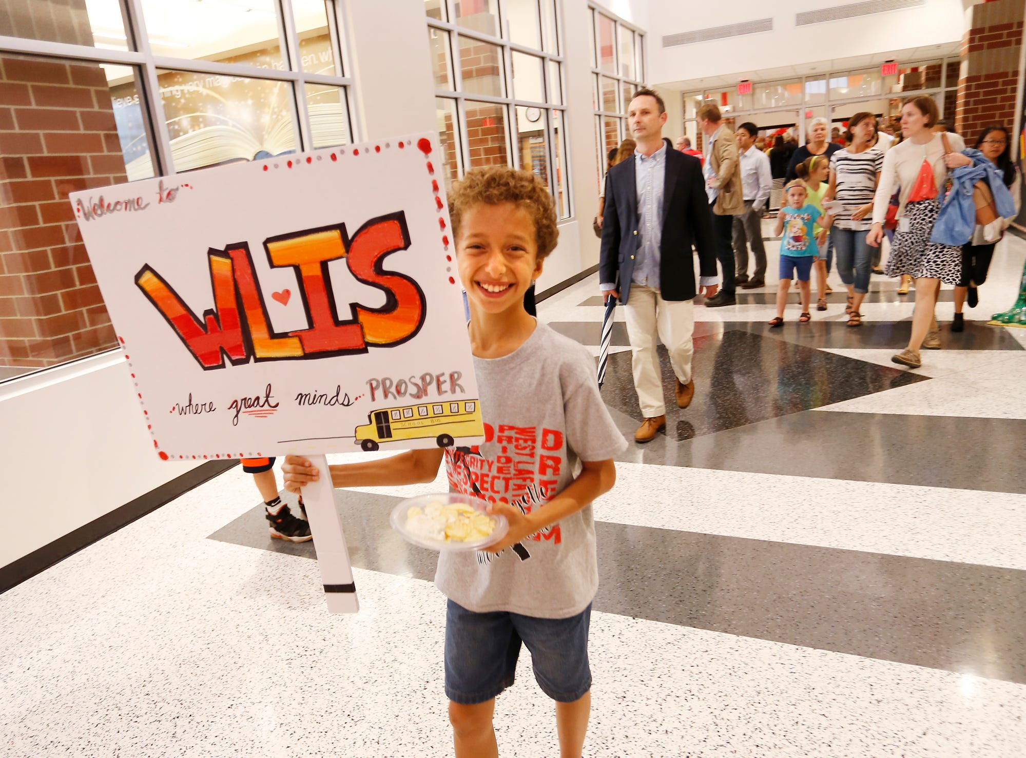 Annas Al-Dubayan, 11, carries a sign as he walks the halls of West Lafayette Intermediate School Wednesday, October 10, 2018, in West Lafayette. Located at Lindberg Road and Salisbury Street, West Lafayette Intermediate School is the first new school building in West Lafayette Community School Corporation since 1961. Al-Dubayan is a sixth grade student.