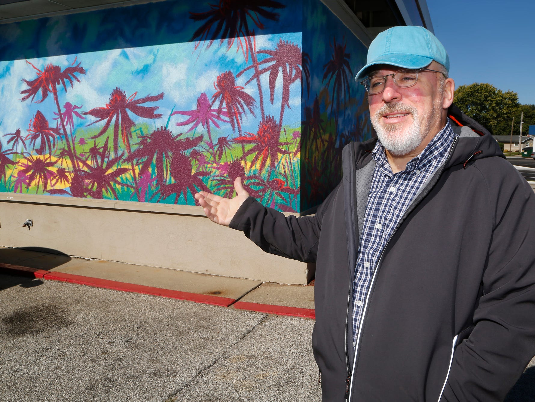 "Artist Craig Martin talks Wednesday, October 17, 2018, about the mural ""Coneflower"" he painted on the side of the Jiffy Lube at the corner of South Street and Earl Avenue in Lafayette. According to Lonnie J. Hinkle, COO of Jiffy Lube of Indiana, there are currently six Jiffy Lube stores that feature murals with six more slated to receive artwork next year. Martin's mural is the only one outside of Indianapolis."