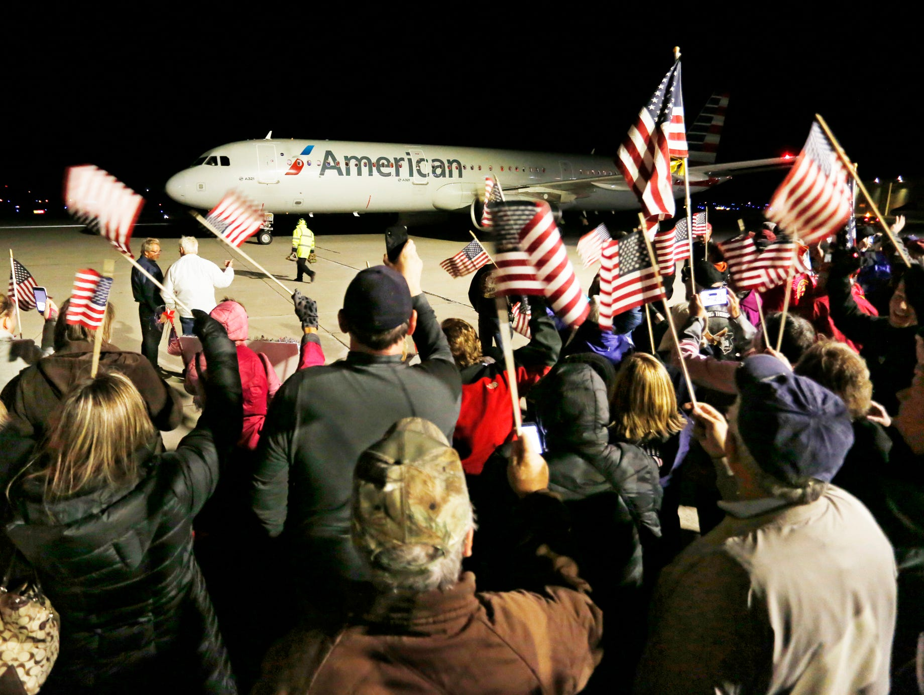 People cheer and wave flags as the final Honor Flight arrives Tuesday, October 16, 2018, at Purdue Airport.