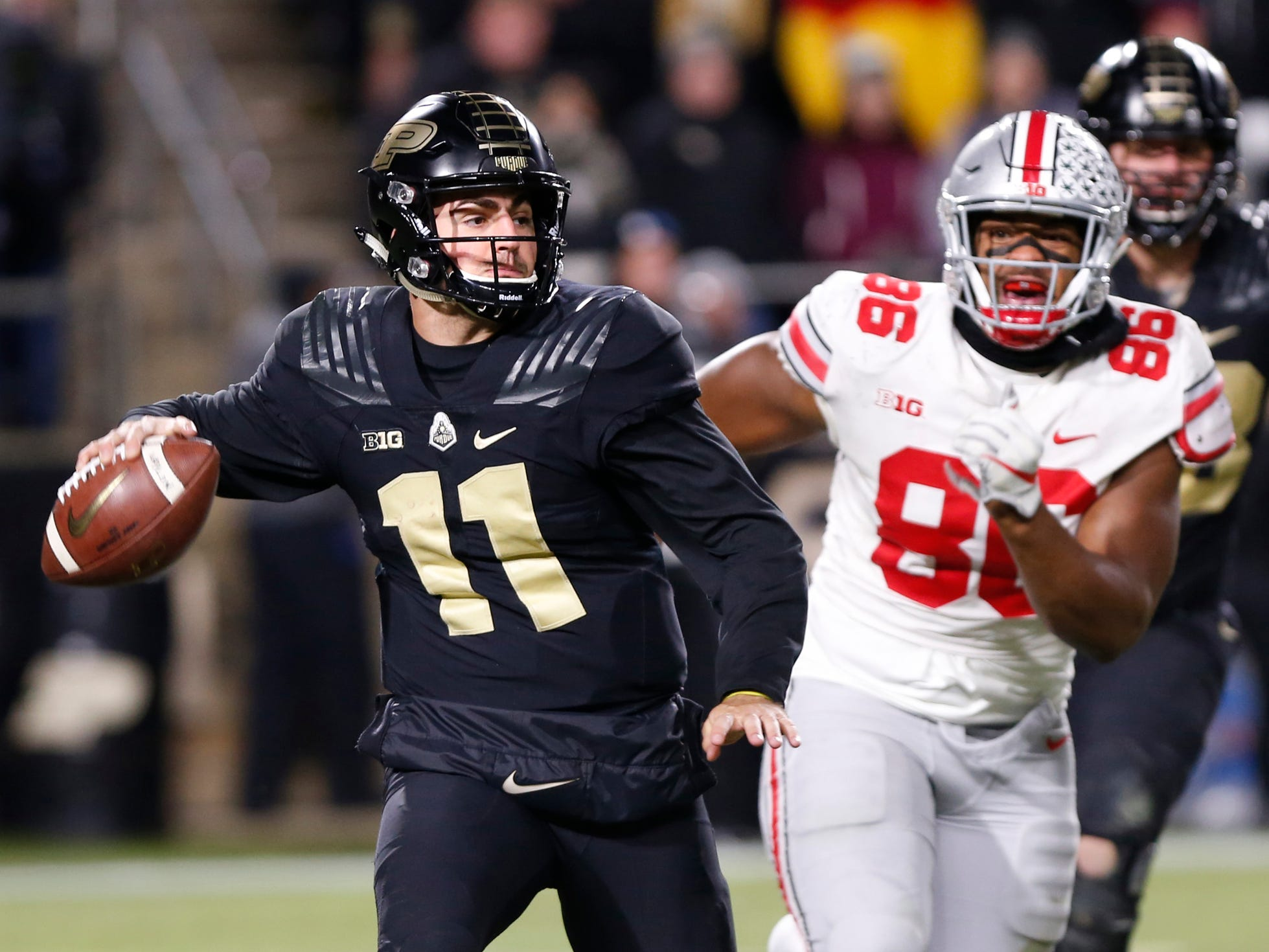Purdue quarterback David Blough rolls out to pass while chased by Dre'Mont Jones of Ohio State Saturday, October 20, 2018, at Ross-Ade Stadium. Purdue upset the No. 2 ranked Buckeyes 49-20.
