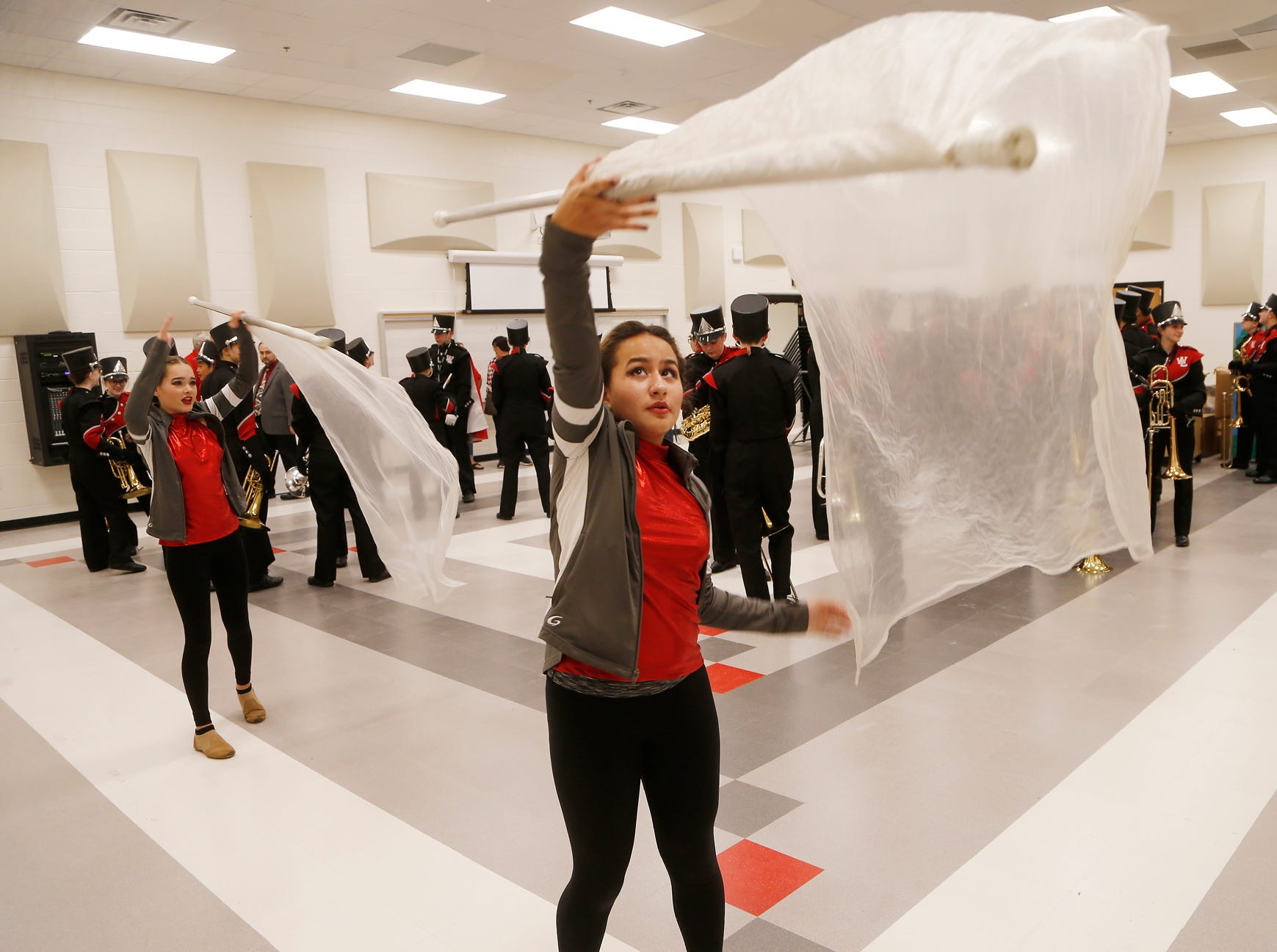 Kendra Noble, 13, foreground, and Leanne Cray, 15, twirl banners as the West Lafayette High School marching band prepares to perform at ribbon cutting ceremonies for West Lafayette Intermediate School Wednesday, October 10, 2018, in West Lafayette. West Lafayette Intermediate School is the first new school building in West Lafayette Community School Corporation since 1961.