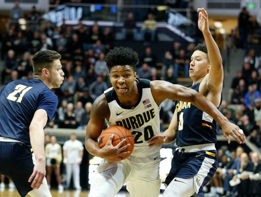 Nojel Eastern of Purdue drives between Cameron Wolter, left, and Sterling Brown of Marian University in the first half Thursday, November 1, 2018, at Mackey Arena.