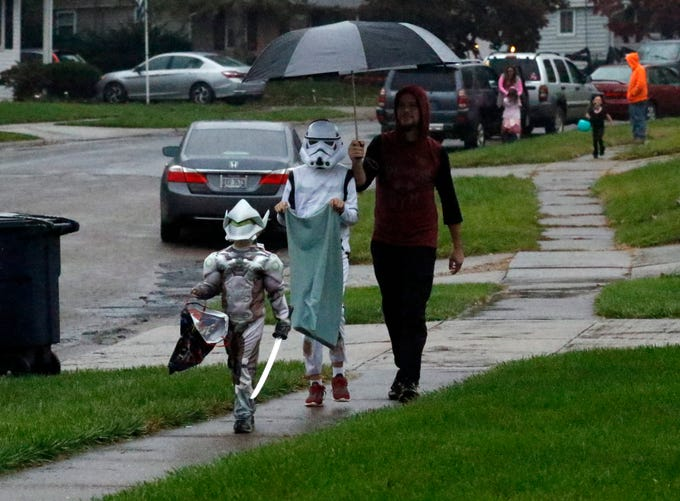 Zach Hill, right, holds an umbrella to shield Daniel Hill, center and Tristan Hill, left, trick-or-treating Wednesday night, Oct. 31, 2018, on Shoshone Drive in Lancaster.