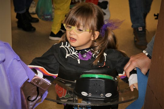 """Lyra Howard participates in trick or treat at Forest Rose School on Wednesday. The students used communicative devices programmed to say """"trick or treat"""" or """"thank you."""""""