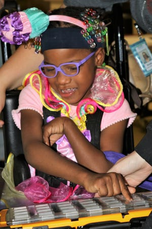 """My'Only Hawkins participates in trick or treat at Forest Rose School on Wednesday. The students used communicative devices programmed to say """"trick or treat"""" or """"thank you."""""""