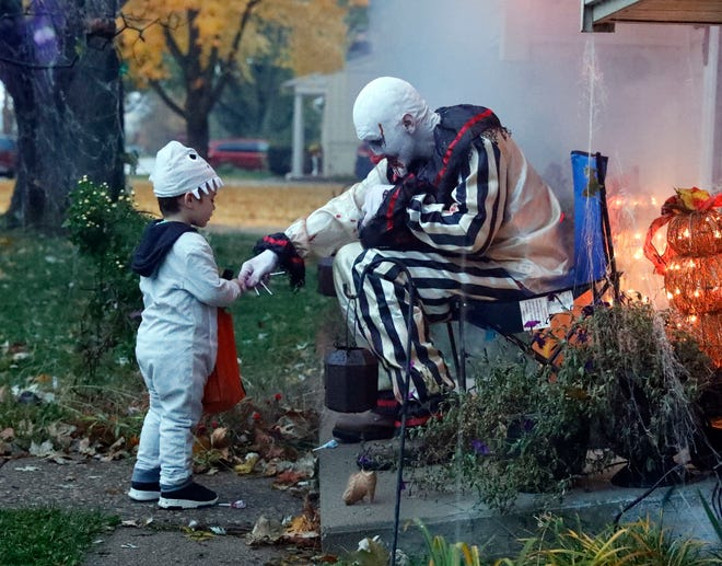 Michael A. Senig, right hands candy to Wyatt Maddux, 3, Wednesday night, Oct. 31, 2018, on Shoshone Drive in Lancaster.