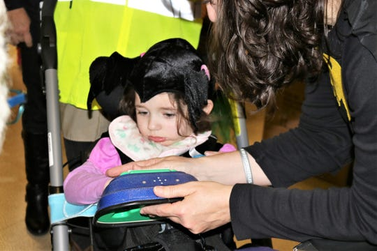 """Adalyn Hillis participates in trick or treat at Forest Rose School on Wednesday. The students used communicative devices programmed to say """"trick or treat"""" or """"thank you."""""""