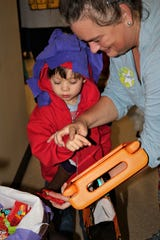 """Aaron Mowan participates in trick or treat at Forest Rose School on Wednesday. The students used communicative devices programmed to say """"trick or treat"""" or """"thank you."""""""