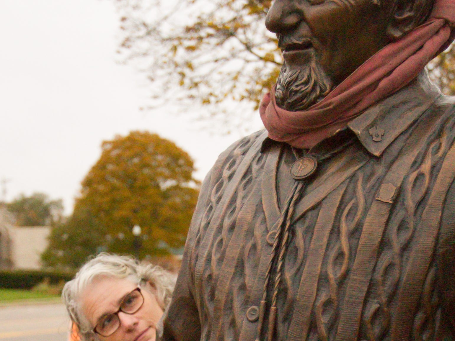 Howell Carnegie District Library director Holly Ward Lamb studies the statue of Duane Zemper, who volunteered countless hours in the archives of the library, as the Zemp Legacy Statue is positioned Thursday, Nov. 1, 2018.