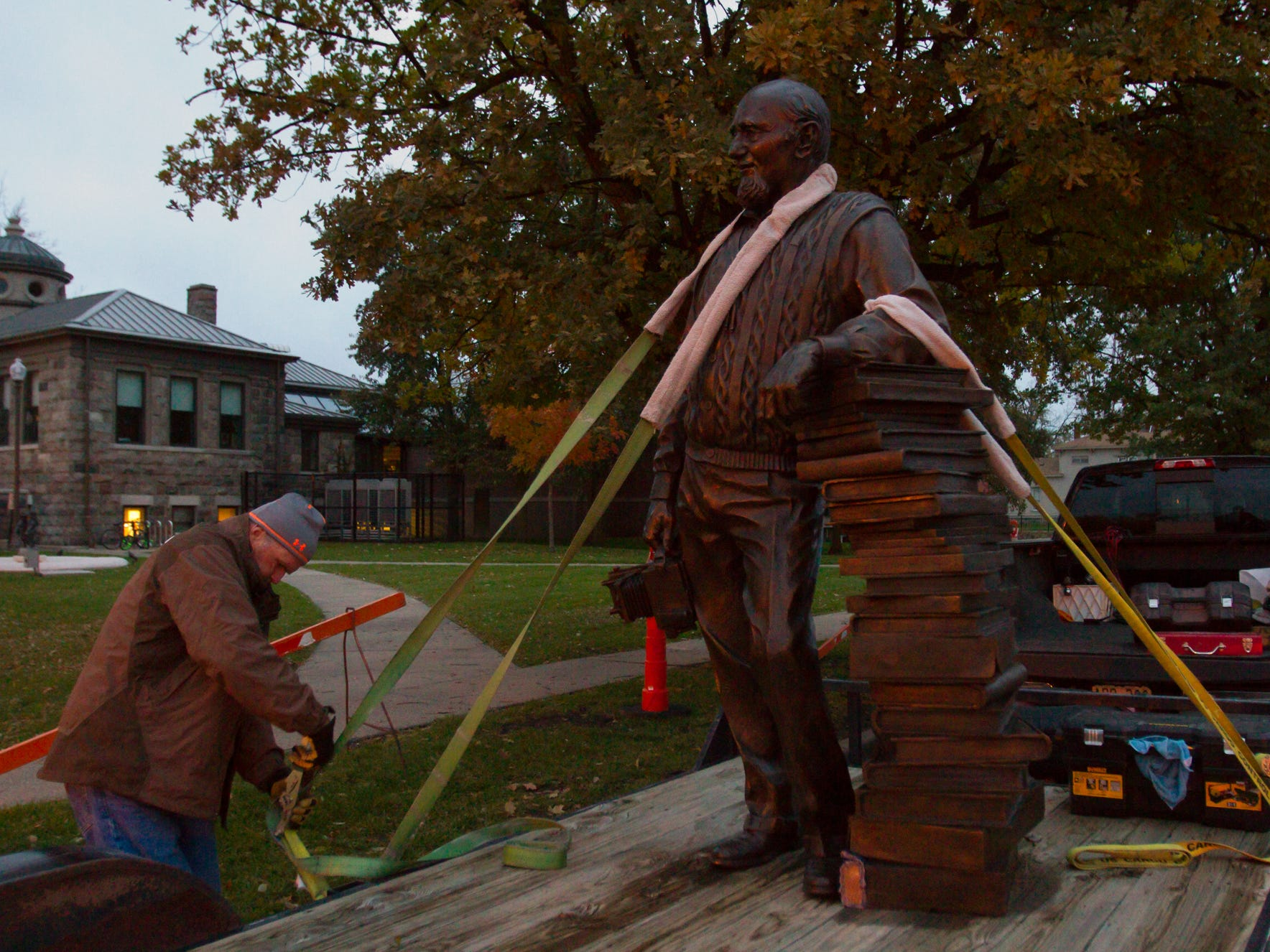 At dawn, Tony Workman, owner of Art Castings of Colorado,  loosens the bindings holding the statue of Duane Zemper being delivered to Howell Carnegie District Library Thursday, Nov. 1, 2018.