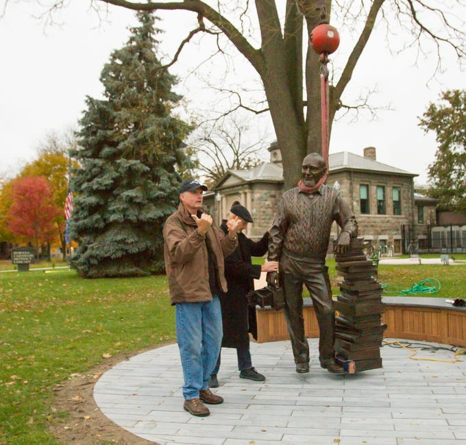 Tony Workman, owner of Art Castings of Colorado, left, signals to a crane operator as sculptor Colin Poole guides the statue of Duane Zemper into position Thursday, Nov. 1, 2018. The statue was unveiled to the public Sunday.