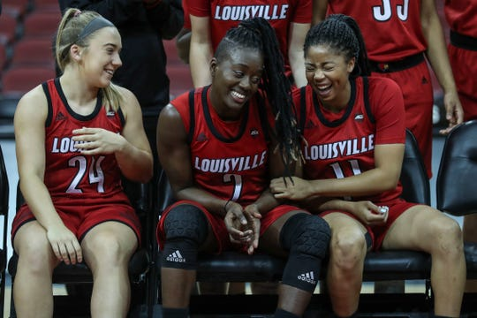Louisville's Yacine Diop, center, laughs with teammates Jessica Laemmle, left, and Arica Carter, right, after a team photo Thursday  at the KFC Yum Center last year.