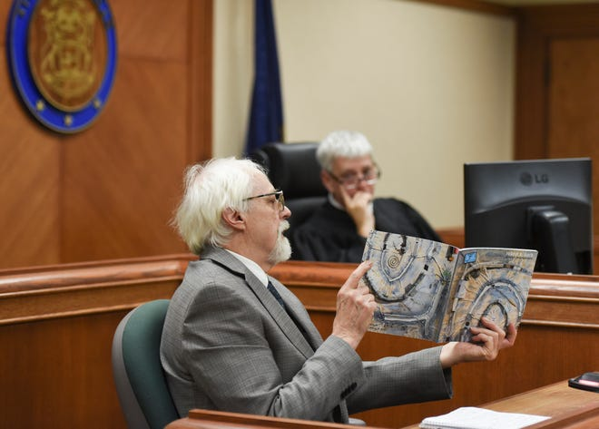 Bath Township artist Robert Park shows a catalog from his show at MSU to Clinton County District Court Judge Michael Clarizio, Wednesday, Oct. 31, 2018, where it talks about his Blue Loop installation. He was given 45 days to remove the items along the pathway of his wooded lot.