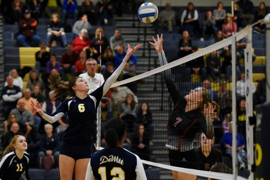 DeWitt's Megan Pozsgai, left, and St. Johns' Kiana Martens approach the net while going for the ball during the third set on Thursday, Nov. 1, 2018, at Owosso High School.