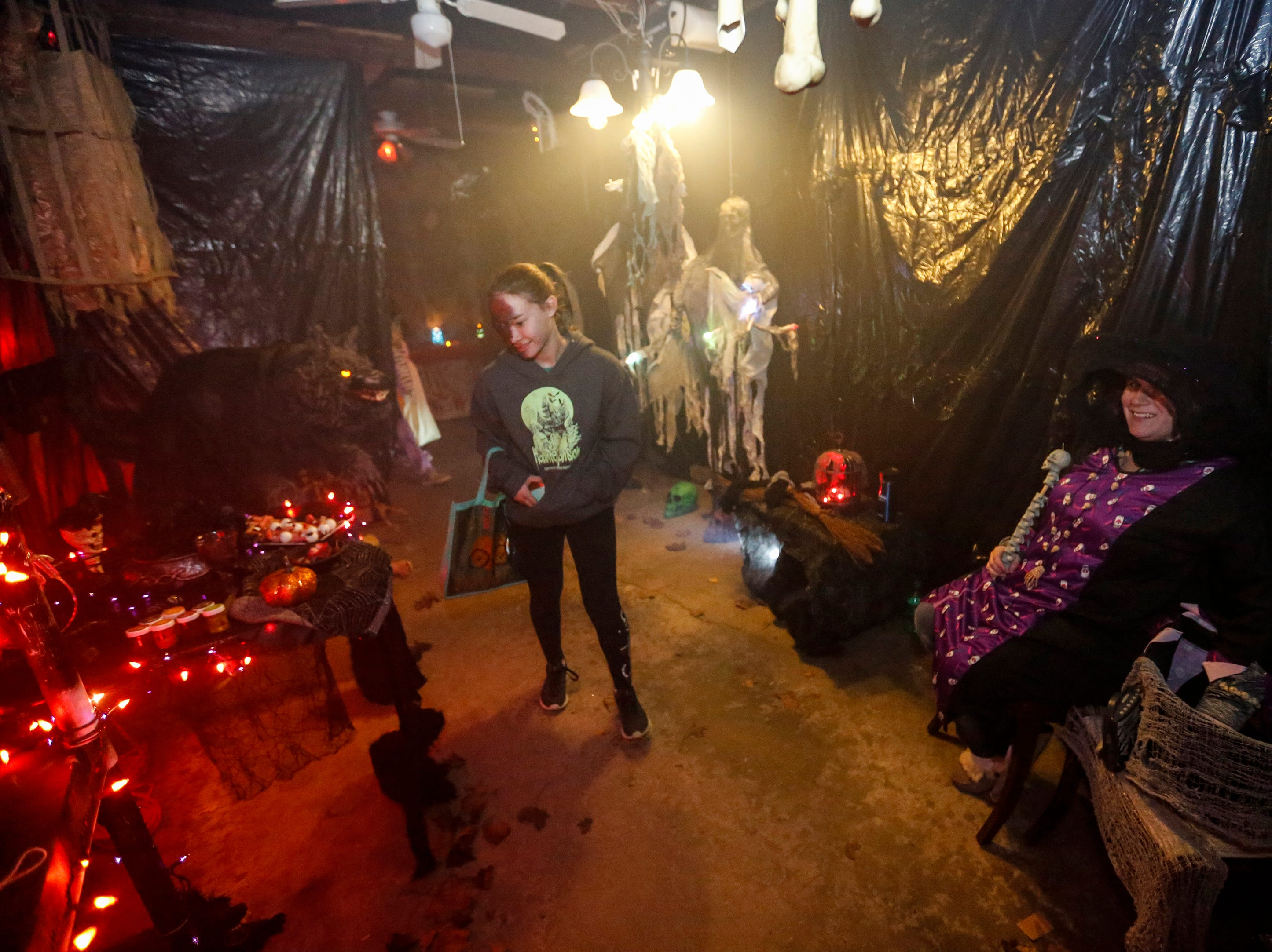 Lea Andures, right, awaits trick-or-treaters making their way through the family's haunted garage on Halloween Wednesday, October 31, 2018, in Manitowoc, Wis. Joshua Clark/USA TODAY NETWORK-Wisconsin