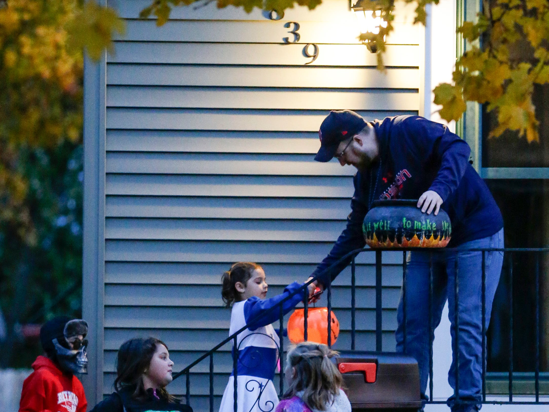 Clint Duzeski hands out candy to trick-or-treaters on Halloween Wednesday, October 31, 2018, in Manitowoc, Wis. Joshua Clark/USA TODAY NETWORK-Wisconsin