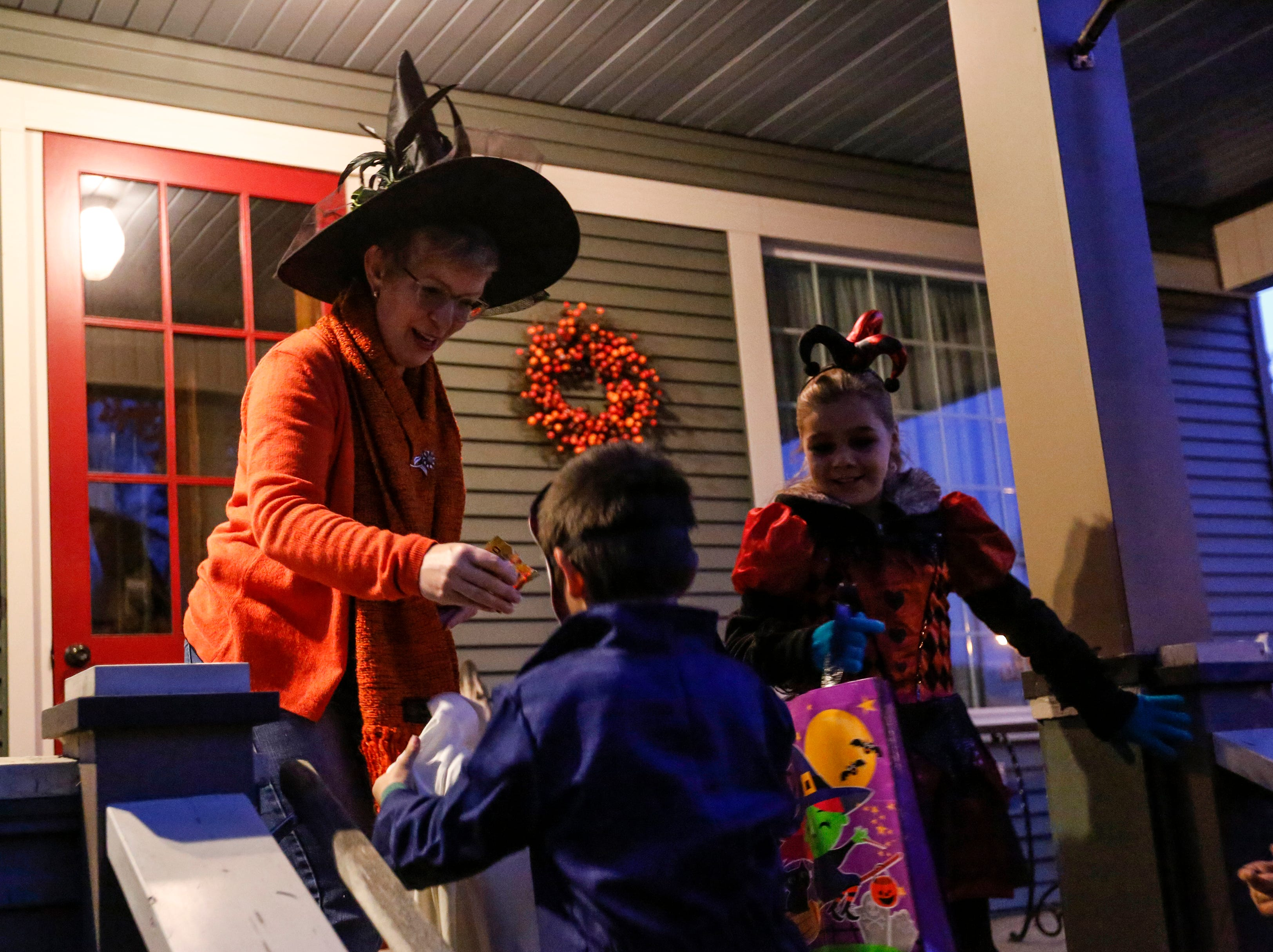 Kristina Schram hands out candy to trick-or-treaters on Halloween Wednesday, October 31, 2018, in Manitowoc, Wis. Joshua Clark/USA TODAY NETWORK-Wisconsin