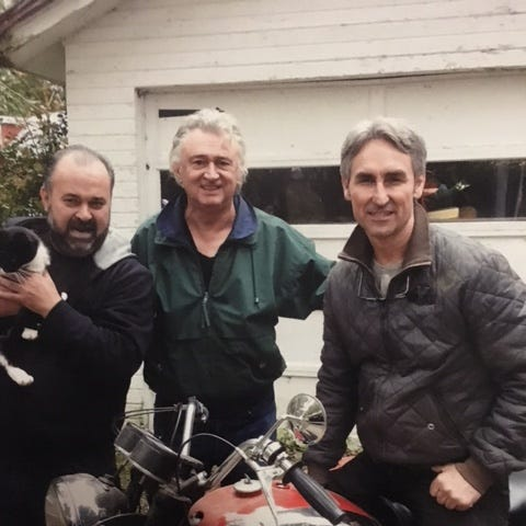 Lexington musician and car collector Timothy Corwin, center, is shown with Frank Fritz and Mike Wolfe, who is holding Corwin's cat Bella, in this photograph last week at his residence.